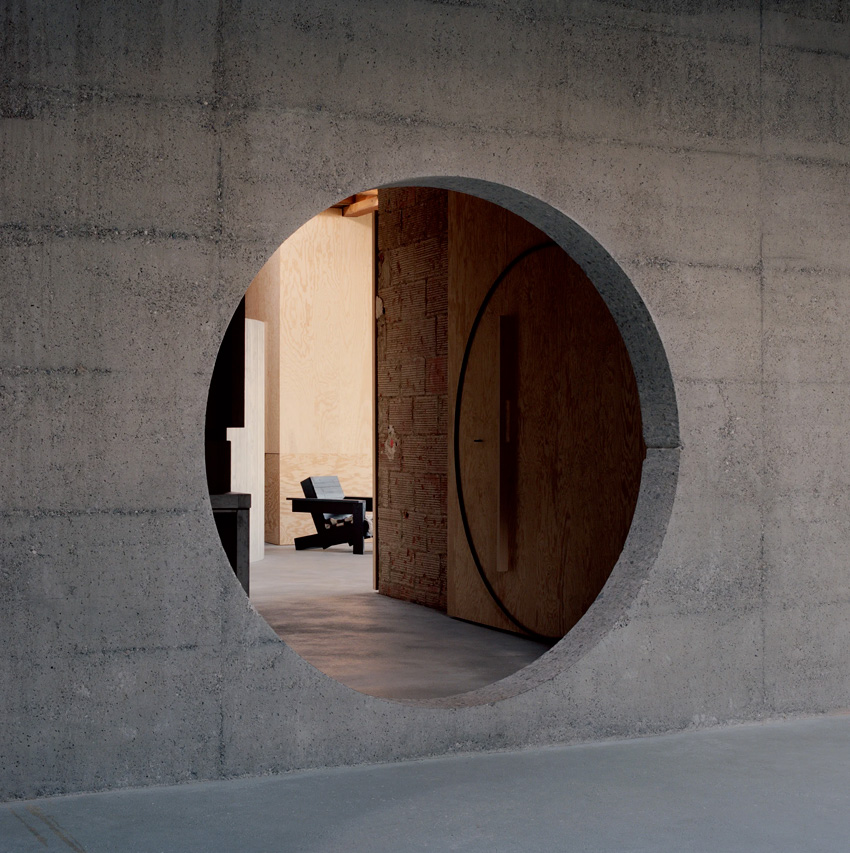 Maison d'architecte en béton, brutaliste, inspiration Paulo Mendes da Rocha. Ouverture circulaire entre les pièces.